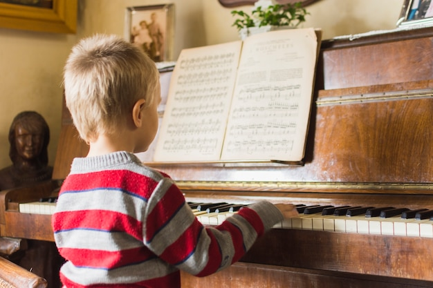 Blonde garçon jouant du piano à la maison Photo gratuit