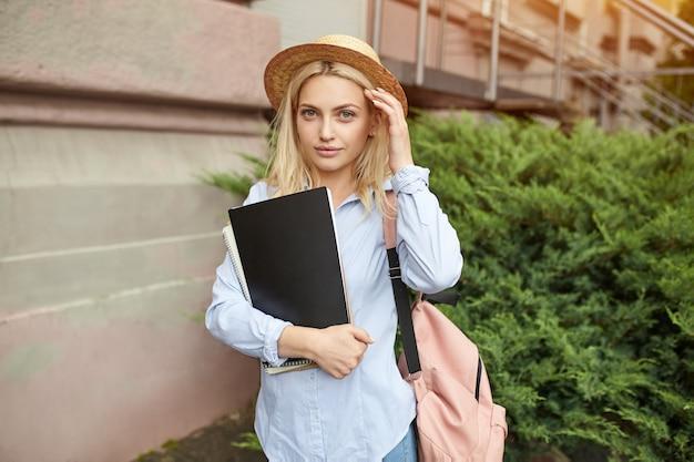 Blonde jeune étudiante dans un chapeau de paille et un sac à dos rose tenant des cahiers. Photo Premium