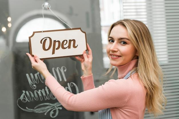 Blonde jeune femme accrochant une balise ouverte sur l'entrée de la porte Photo gratuit