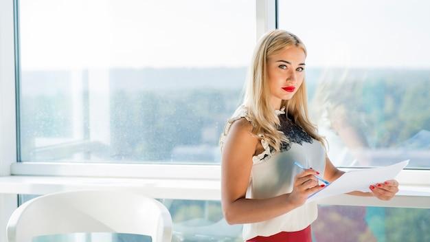 Blonde jeune femme d'affaires détenant un document dans le bureau Photo gratuit