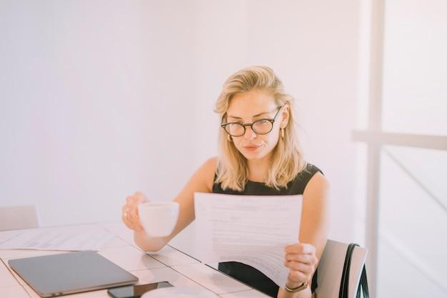 Blonde jeune femme d'affaires détenant une tasse de café en lisant le document sur le lieu de travail Photo gratuit
