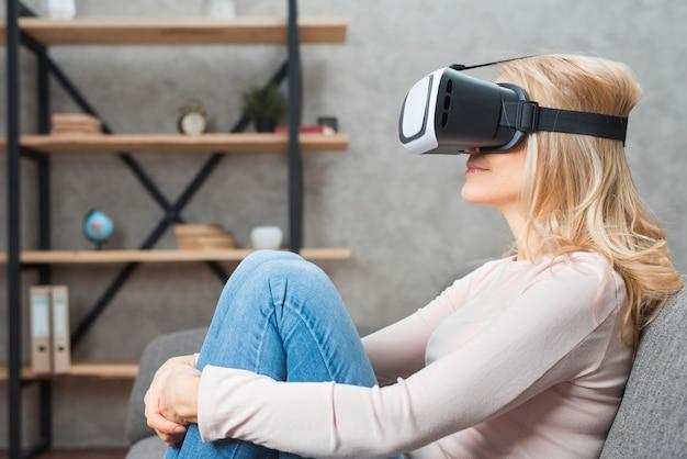 Blonde jeune femme assise sur le canapé portant des lunettes de réalité virtuelle Photo gratuit