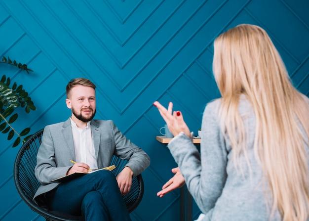 Blonde jeune femme assise devant son psychologue discutant de ses problèmes Photo gratuit