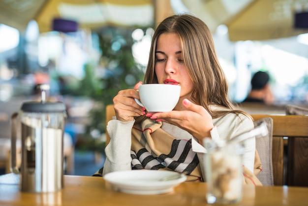Blonde jeune femme buvant de la tisane en tasse blanche Photo gratuit