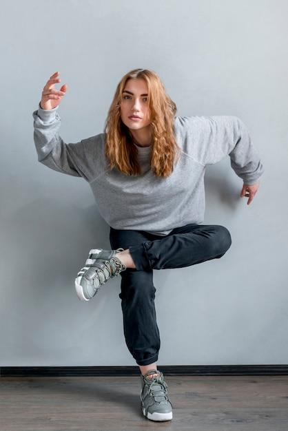 Blonde jeune femme debout sur un pied contre le mur gris Photo gratuit