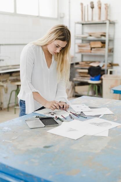 Blonde jeune femme dessinant sur du papier blanc en atelier Photo gratuit