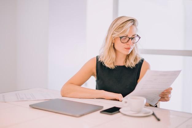 Blonde jeune femme lisant le document sur le lieu de travail avec une tasse de café; ordinateur portable et téléphone portable sur la table Photo gratuit