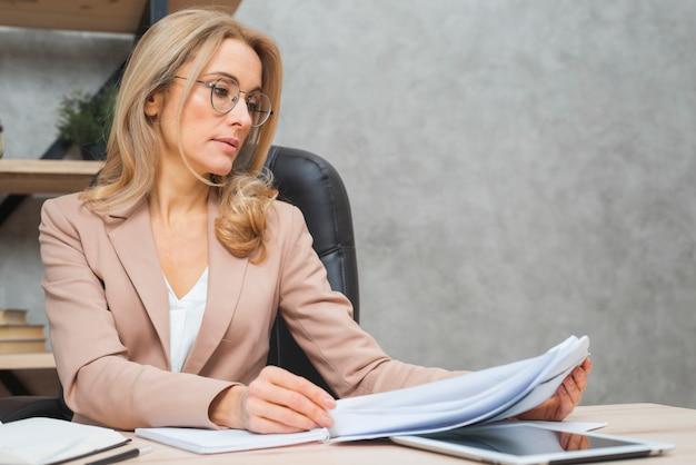 Blonde jeune femme lisant les documents sur le lieu de travail Photo gratuit
