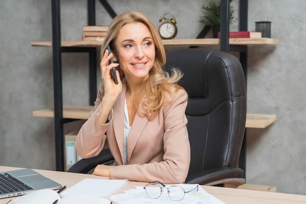 Blonde Jeune Femme Parlant Au Téléphone Assis Sur Une Chaise Au Bureau Photo gratuit
