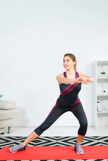 Blonde jeune femme pratiquant des exercices d'étirement à la maison Photo gratuit