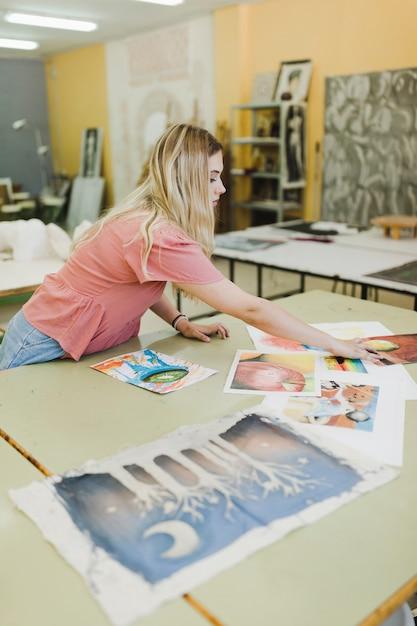 Blonde Jeune Femme Regardant Des Peintures Sur établi Photo gratuit