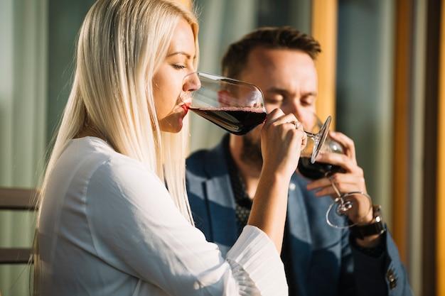 Blonde jeune femme et son petit ami buvant un verre de vin rouge Photo gratuit