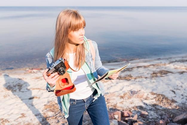 Blonde jeune femme tenant une caméra vintage et carte en main debout à la plage Photo gratuit