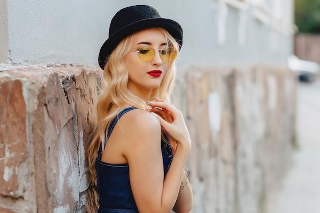 Blonde jolie fille à lunettes de soleil et un chapeau élégant au soleil d'été urbain Photo Premium