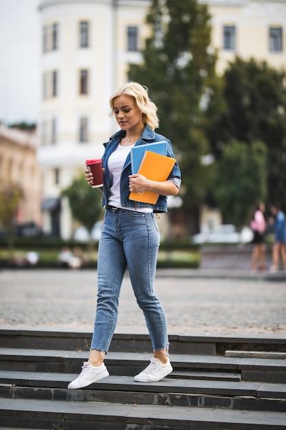 Blonde Modèle Fille Souriante Va Aux Classes De Travail à Travers Le Centre-ville Tenant Un Ordinateur Portable Dans Ses Mains Le Matin Photo gratuit