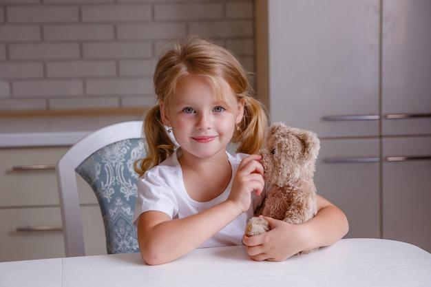 Blonde Petite Fille Avec Ourson Dans La Cuisine Avant De Se Coucher Photo Premium
