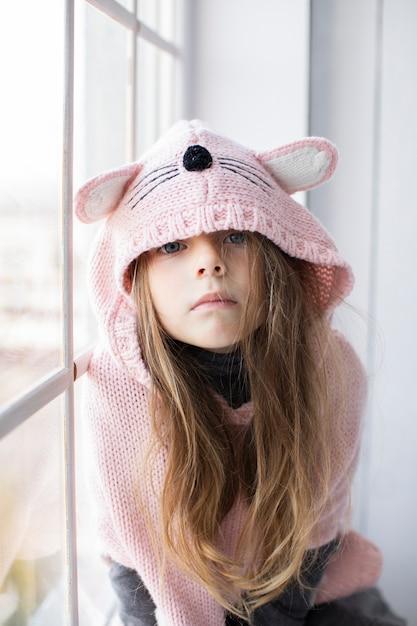 Blonde petite fille portant un pull rose Photo gratuit