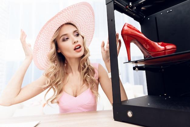 Blonde en robe rose regarde une chaussure rouge dans une imprimante 3d. Photo Premium