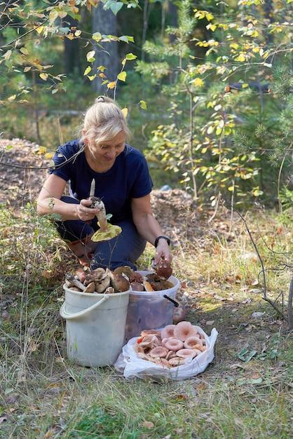 La Blonde S'assoit Dans La Forêt Devant Les Champignons Récoltés. Une Femme Tient De Gros Cèpes Dans Ses Mains. Tir Vertical Photo Premium