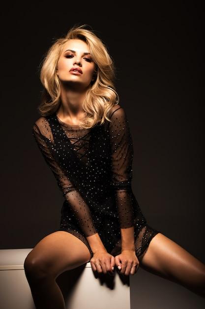 Blonde sexy dans une robe élégante sur un noir Photo Premium