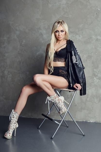 Blonde sexy en lingerie noire et veste en cuir Photo Premium
