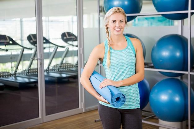 Blonde souriante tenant un tapis de yoga dans la salle de fitness Photo Premium