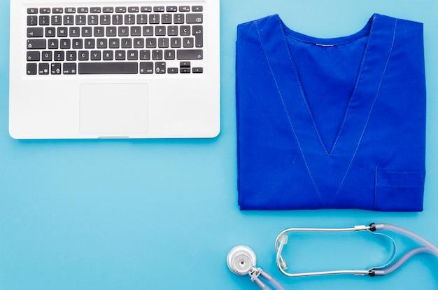 Blouse de médecin bleue; stéthoscope et ordinateur portable sur fond bleu Photo gratuit