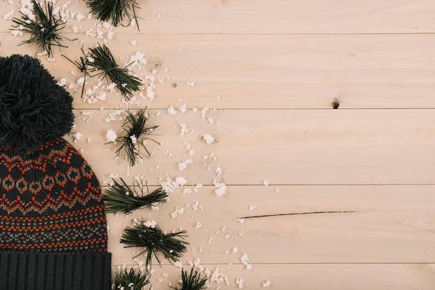 Bobble hat près de la neige et des aiguilles de sapin Photo gratuit