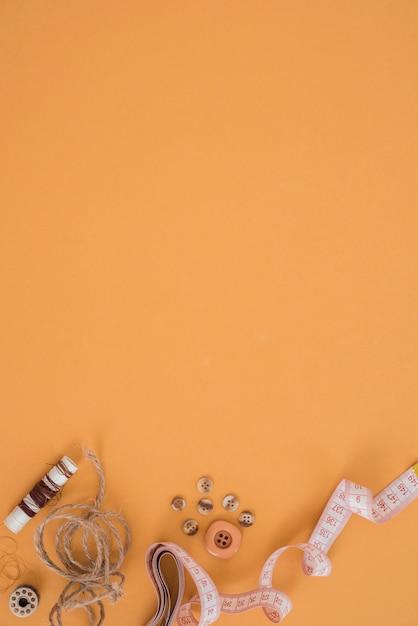 Bobine; chaîne de jute; bouton et ruban à mesurer sur un fond orange Photo gratuit