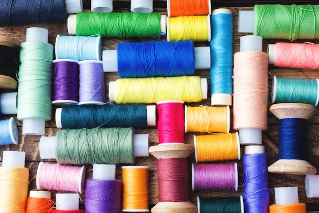 Bobines de fil de couleur disposées en rangées sur une surface en bois Photo Premium