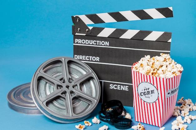 Bobines de film; bandes de film et clap avec boîte de pop-corn sur fond bleu Photo gratuit
