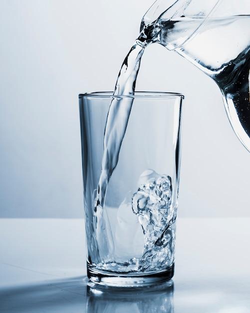 Bocal Remplissant Un Verre D'eau Photo gratuit