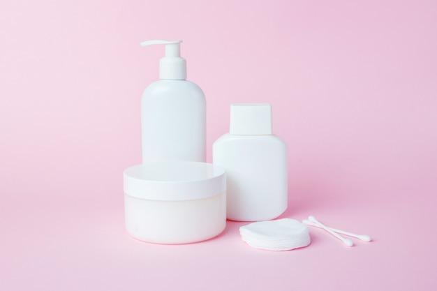 Bocaux blancs de cosmétiques sur rose Photo Premium