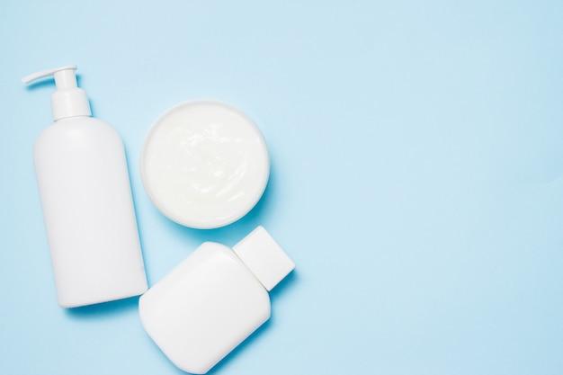 Bocaux blancs de produits de beauté sur un bleu. accessoires de bain. Photo Premium