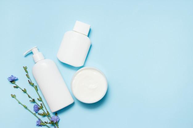 Bocaux blancs de produits de beauté avec des fleurs sur fond bleu Photo Premium