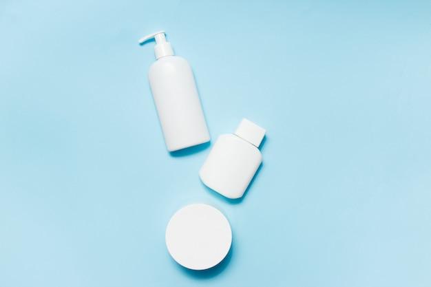 Bocaux blancs de produits de beauté sur fond bleu Photo Premium