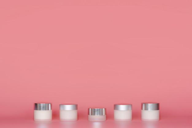 Bocaux ronds de crème cosmétique permanent sur fond rose. Photo Premium