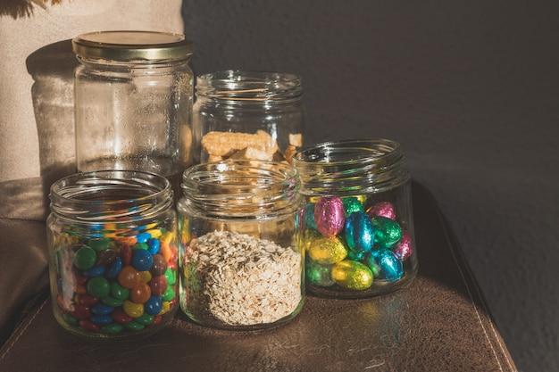 Bocaux en verre avec des bonbons au chocolat, avoine, miel, biscuits et chocolats Photo Premium