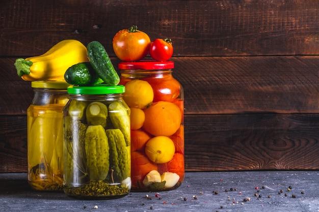 Bocaux en verre de concombres frais marinés, courgettes et tomates sur un fond en bois. espace de copie. Photo Premium