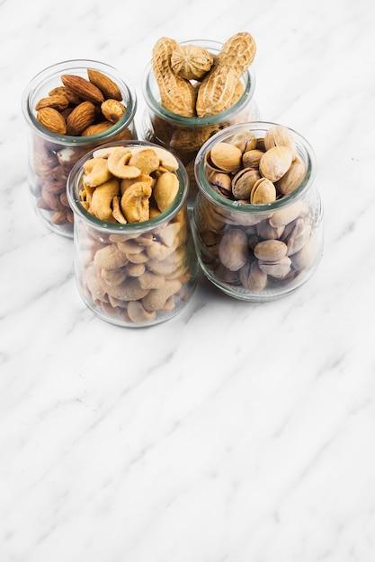 Bocaux en verre remplis de noix aux fruits sur fond de marbre Photo gratuit
