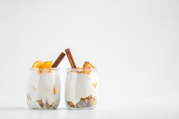 Bocaux de yaourt grec au granola, cannelle et abricots en conserve Photo Premium