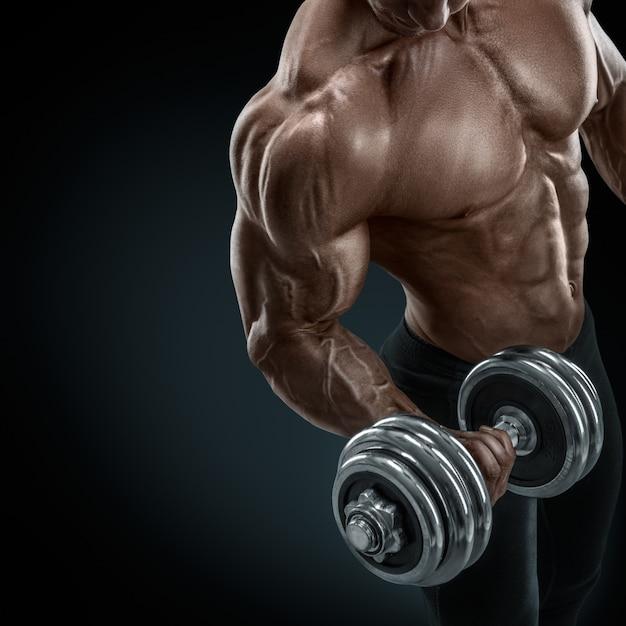 Bodybuilder fort et puissant, faire des exercices avec haltère Photo Premium