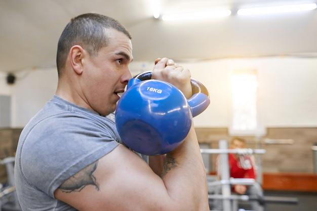 Bodybuilder jeune athlète musculaire fort lève des poids Photo Premium