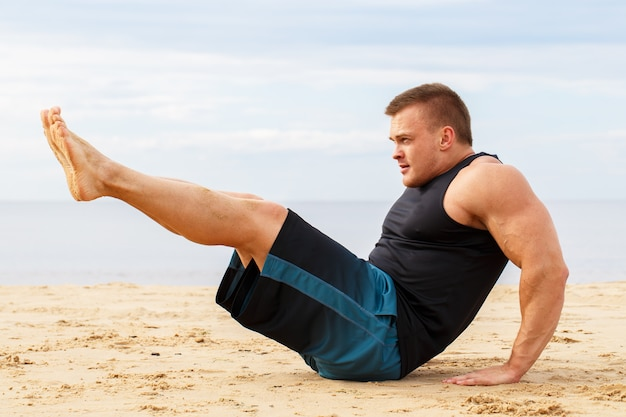 Bodybuilder sur la plage Photo gratuit