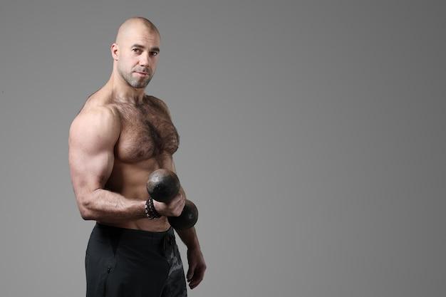 Bodybuilder Posant Et Montrant Les Muscles Photo gratuit