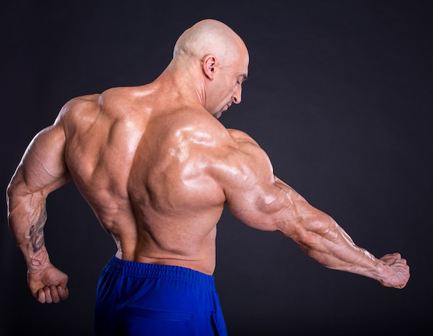 Bodybuilder pose, montrant ses muscles. Photo Premium