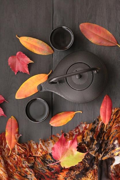 Boire du thé en automne. humeur de thé en automne. théière noire et feuilles d'automne Photo Premium