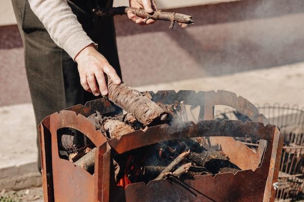Bois De Chauffage Dans Le Grill. L'homme Allume Un Feu De Joie Pour Griller La Viande. Photo gratuit