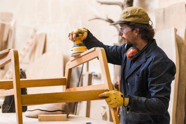 Bois de ponçage de charpentier avec polisseuse électrique Photo gratuit
