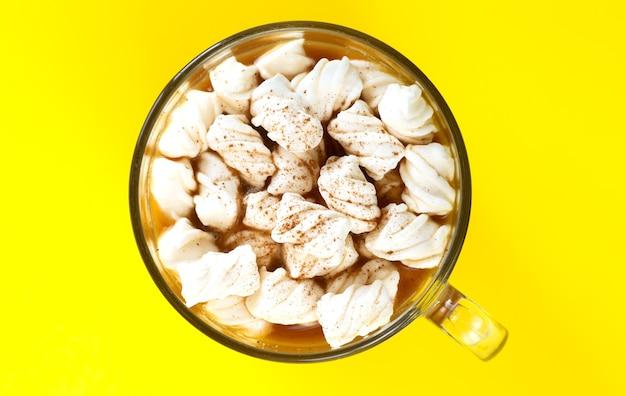 Boisson Au Cacao Avec Des Guimauves Et Du Chocolat En Poudre Dans Une Tasse En Verre Sur Fond Jaune Vue De Dessus Photo Premium